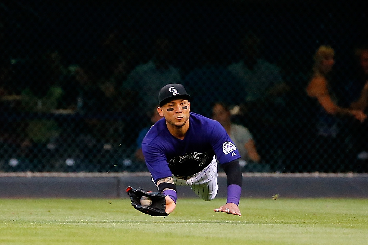 DENVER, CO - SEPTEMBER 02:  Rightfielder Carlos Gonzalez #5 of the Colorado Rockies makes a diving catch on a sacrifice fly by A.J. Pollock #11 of the Arizona Diamondbacks to score Ender Inciarte #5 of the Arizona Diamondbacks to take a 1-0 lead in the first inning at Coors Field on September 2, 2015 in Denver, Colorado.  (Photo by Doug Pensinger/Getty Images)