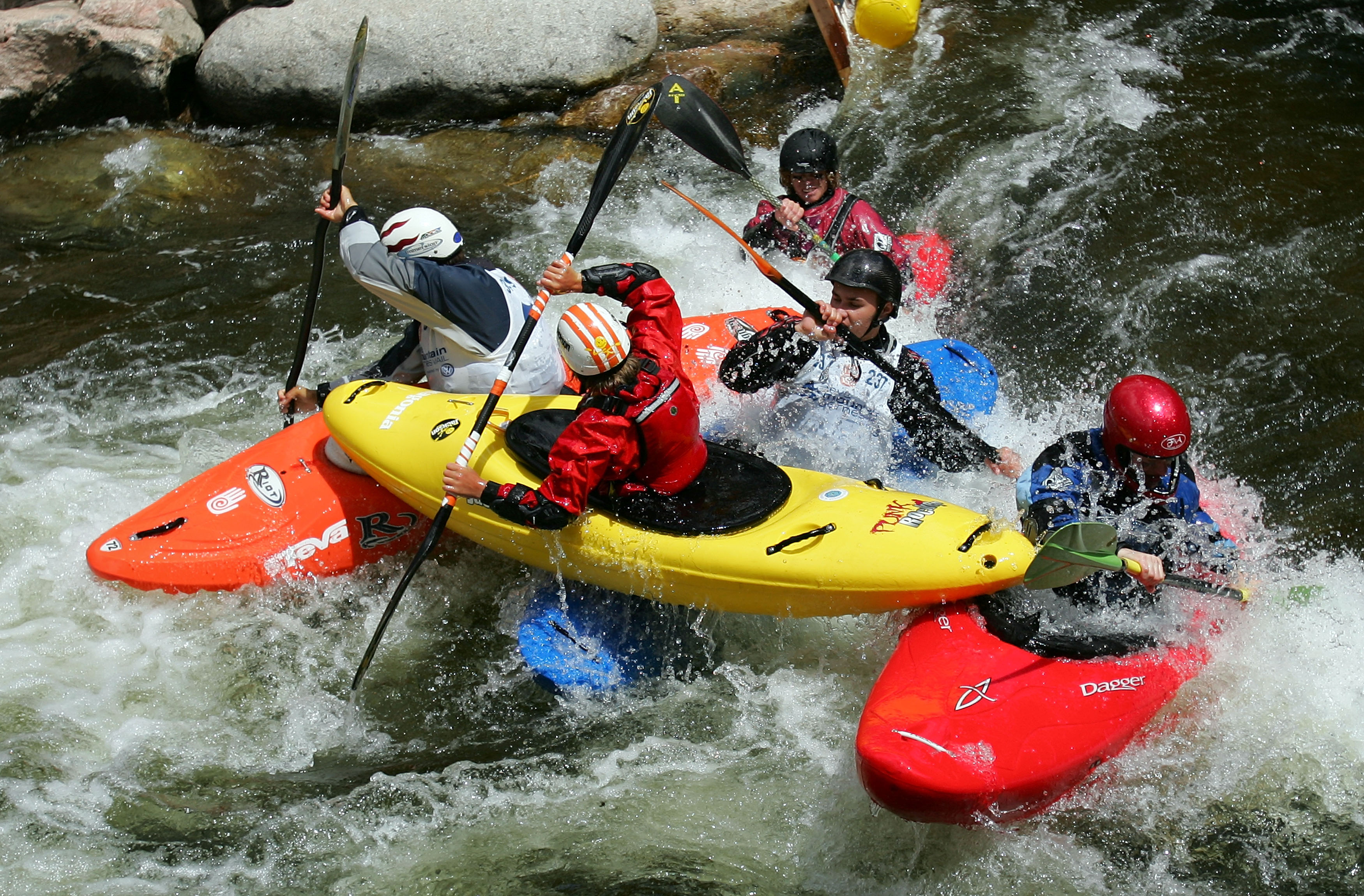 VAIL, CO - JUNE 3:  Kayakers collide during the 8 Ball Kayak Sprint during the 8 Ball Kayak Sprint during the Teva Mountain Games June 3, 2007 Competitors, in white bibs, sprint head to head downstream as the 8 Balls impede their progress enroute to the finish. Featured 8 Ball Dane Jackson, age 13, of Walling, Tennessee is hoisted out of the water by charging Kayakers during the semifinals.  (Photo by Doug Pensinger/Getty Images)